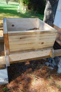 """first box with a permanent entrance and a natural branch wedged inside as a comb support. The ½"""" offset between the dimension of the basement and the perimeter of the supers lock the floating mesh floor in place and provide some stability to the hive."""