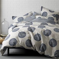 Artistic duvet cover and sham with sundial motif on a textural stone-colored ground. Woven of 100% certified organic cotton. 200-thread count.