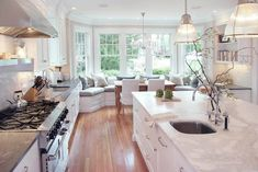 Look at all of the windows!! I also love the light fixtures. Chandeliers in kitchen are a fabulous idea.