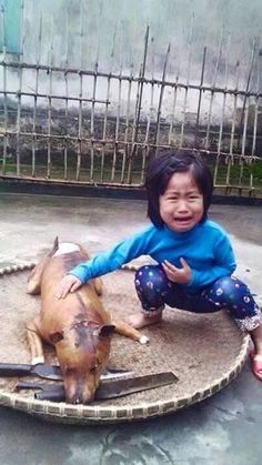 Traumatised: The small girl crying next to what is thought to be her roasted dog
