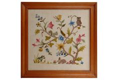 """Framed crewel work piece with a tree filled with leaves, flowers and creatures in a variety of crewel work techniques. Blue, pink and gold flowers, with a butterfly, a squirrel, a fuzzy caterpillar, an owl, a rabbit, and a leaping frog. Signed """"VAM."""" Worked on raw linen, displayed in a cherry-colored wood frame."""