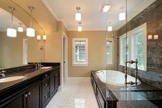 Passend zu dunklen Eitelkeit Theken oben unter Waschbecken Schränke und rund um die Badewanne. Sie bilden einen schönen Kontrast zu der Creme farbige Wand- und gepunkteten weißen.