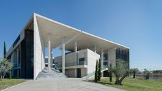 Angled walls and openings break up mass of concrete office building by Vtria Architects