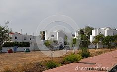 Photo taken near Gata Bay in Andalusia (Spain). The photo, taken from an adjacent street, picks up some modern houses surrounded by a few slender trees and some cars parked on the lawn that stretches from housing to the street.