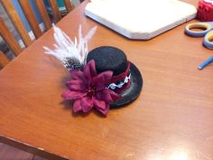 My baby gir's hat for the Belmont Stakes race (it's tiny, about the size of a small fist).  A fluffy feather piece with two kinds of feathers, red lace and black and white rosette trim around the band, with a burgundy and red flower.