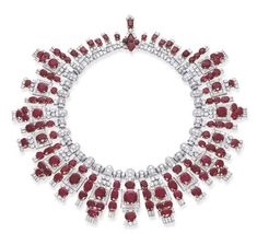A MAGNIFICENT ART DECO RUBY AND DIAMOND NECKLACE, BY CARTIER   Designed as an oval and cushion-cut ruby and baguette-cut diamond graduated fringe with brilliant-cut diamond detail to the pavé-set and baguette-cut diamond links and rectangular-cut ruby backchain, 36.4 cm. long, with fitted red leather Cartier case  By Cartier