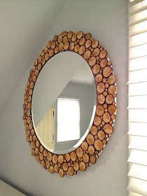 Round mirror on plywood with wooden discs cut from tree branch glued to board surrounding mirror