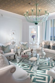 Loving that peppermint green & white rug & all of the accessories surrounding it, that incredible glass chandelier, those velvet cushions, the black piping on the single striking armchairs, the gold studding on the sofas, ohh we can't stop, it's just endless....