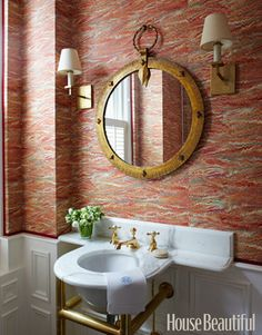 Antique French Bathroom:   Marbleized paper — Pheasant by Twigs — and a 1940s French metal mirror complement this powder room's vintage marble sink and antique fixtures. Design by Todd Klein. See the entire high gloss home.