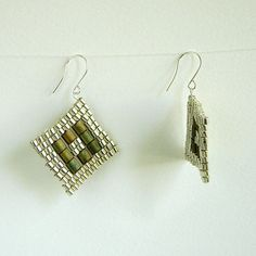 These Art Deco inspired earrings have a contemporary twist and are simple and stylish in their design! I weaved these earrings using a flat square stitch. A square tile of metallic silver Delica seed-beads' band surrounds 15 x 15 mm square of metallic matte sage rainbow Miyuki Tila seed beads. This feather-weight 1 x 1 inch square tile dangles playfully of silver plated fishhook ear wire. Metallic silver beads are being complemented by the grayish green matte rainbow square Tila seed beads…