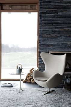Arne Jacobsen Egg chair in white by slate fire place. A great spot for reading. Use Bellstone's stackstone to achieve the same look. www.bellstone.com.au
