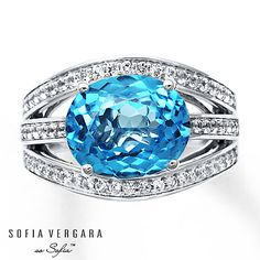 This thrilling ring for her from the SOFIA VERGARA so Sofia™ collection features an oval natural blue topaz complemented by rows of natural white topaz gemstones set in sterling silver. Two natural emeralds are bezel-set into the profiles of the ring to complete the signature look.  Most natural gemstones pictured have been subject to an enhancement process or treatment (e.g. heating, oiling, diffusion, waxing, etc.), which may not be permanent and may require special care.  Generally, most…