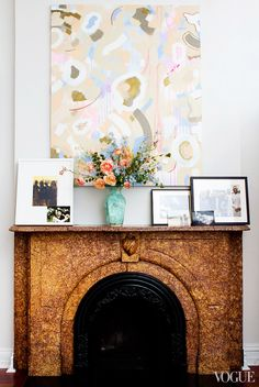 Pastel-colored artwork above fireplace with vase of flowers and leaning frames