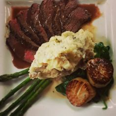 Surf & turf - 8-10 oz baseball sirloin topped with a demi glacé & pan seared scallops topped with a citrus beurre blanc. Served with smashed potatoes and sautéed spinach and arugula