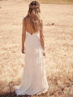 Tiered Lace Maxi | This dress is delicate and feminine. The wrapped bodice is made up of lace and a subtle floral applique. The silk body is covered in tiered eyelash lace. Hidden zip in back with a hook and eye closure. Low back. Lined. *By Erin Fetherston