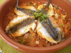 Cómo hacer Moraga de Sardinas a la Malagueña. Cortamos en rodajas los tomates, la cebolla, el pimiento. Hacemos una picada con los ajos, las hojas de perejil, el vino blanco y el