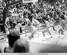 Black and white photo of action during a University of Oregon basketball game against UCLA played at McArthur Court on February 16, 1974 and won by the Ducks 56-51. From left to right are: Gerald Willett (#50), Bruce Coldren (reaching for the ball), Mark Barwig (behind Coldren), Greg Ballard (#42), and Ronnie Lee (#30). At far left is UCLA's Bill Walton. ©University of Oregon Libraries - Special Collections and University Archives