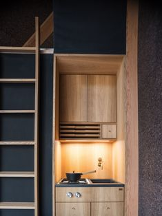 Upon entering is a single space with ample glazing. A Morsøe wood-burning fireplace is nestled in one corner, while a small kitchenette is designed with light wood cabinetry by furniture makes Københavns Møbelsnedkeri.