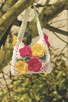 Floral crochet bag | TheMakingSpot - worked in Texere's Prism Optic smooth acrylic yarn in Magenta, Sunshine, Green Fir and the base colour of choice, using a 3mm hook.  Designed by Heather Kingsley-Heath. The pattern was published in Simply Knitting magazine, but I don't know which issue.