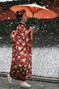 Geisha (Japanese traditional dancers) walk in the snow at Gion on January 7, 2006 in Kyoto, Japan.