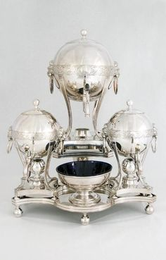 Tea Machine, ca.1798, Old Sheffield Plate, glass. Made by Daniel Holy, Wilkinson & Co; slop basin by Roberts, Cadman & Co. Consists of a large central hot-water urn that holds 6 pints of water. The large urn can turn to supply the 2 smaller urns, that hold 3 pints each. One small urn is for coffee & one for tea. All the urns can be taken off the frame to be used separately.