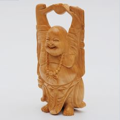 This figurine made from Kadam wood is the Laughing Buddha of Prosperity holding up a 'Ru-Yi Pot' or Bowl of Plenty up to the universe to receive abundance. The Laughing Buddha statues are considered propitious according to Feng Shui. Perfect to gift or keep as a symbol of receiving profusion and luck from the cosmos.