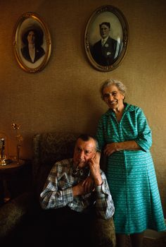 An elderly couple poses beneath their youthful portraits September 1975. Photograph by James L. Stanfield