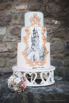 Fairytale castle wedding cake. Handpainted design with gold detail. Blue and blush pink airbrush ombre effect. Wedding | Cemlyn Cakes | Portishead | Church Stretton