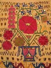 """Tsevres from Thrace - """"vase of life"""" with poppies and cypress trees. Silk thread, gold wire on cotton -Counted thread stitch.  The Greek Institute"""