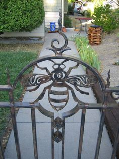 A garden gate designed to blend a whimsical motif with classic iron details that wouldn't look out of place in front of a 100 year old craftsman bungalow. Gate is steel with a three coat wip…