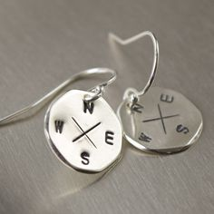 Sterling silver compass earrings featuring North, South, East and West. All impressions are stamped by hand then blackened to accent the detailing. The blackened accents have been sealed with a very l
