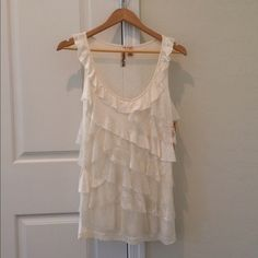 """Lace ruffle ivory top Sleeveless lace ruffle top.  No ruffles in back. 100% rayon, contrast trim: 90% nylon, 10% spandex. 15"""" armpit to armpit, 26"""" back of neck to bottom. There is some stretch to the jersey material. The neckline is low. You can pair a camisole underneath it. New with tags. Eyeshadow Tops"""