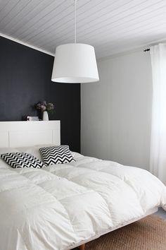 Az különleges mintájú párnák, melyek harmonizálnak a fal színével érdekessé teszik ezt az egyszerű szobát.