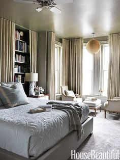 Hang curtains to hide a bookshelf. Design: Barry Dixon. housebeautiful.com