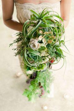 Voilà un bouquet de mariée extrêmement original et assez exotique ! Il est majoritairement composé de plantes grasses, avec très peu de fleurs. La couleur verte est donc majeure dans ce bouquet. Il sera parfait pour vous si tout ce monde rose-rouge ce n'est pas trop votre truc, et s'accordera bien avec une robe beige, écru ou du moins blanc cassé.