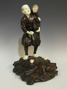 Fine bronze and ivory figure of an elderly gentleman with child on his shoulders and cockerel under his arm on a carved wooden, Japan, Meiji period