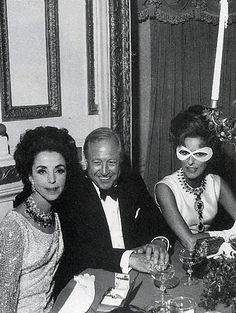 At Truman Capote's masked ball, Bill Paley beams between Gloria Guiness and his wife, Babe. @ Vogue.