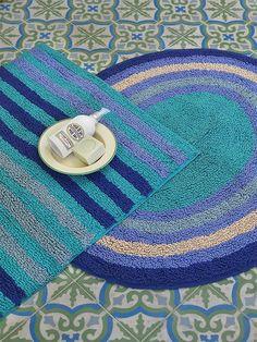 Herbst / Winter 2012 - Frotteeteppiche aus Baumwolle: Die Türkis- und veilchenfarbenen gestreiften Teppiche sind aus weichem Baumwollflausch und haben eine Latexbeschichtung auf der Rückseite, damit sie nicht verrutschen können. Die Teppiche gibt es in runder und eckiger Form.