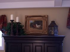 armoire top decorating idea - plant, candle sticks, framed picture, lantern
