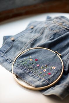 DIY Embroidered Embellished Jean Jacket by Anne Weil of Flax & Twine Fabulous DIY embellished jean jacket for a unique, personalized back to school wardrobe staple. A combo of applique patches + hand embroidery make it custom Embroidery On Clothes, Embroidered Clothes, Embroidery Fashion, Hand Embroidery, Embroidery Designs, Diy Embroidered Jeans, Embroidered Jacket, Denim Jacket Embroidery, Diy Embroidery On Jeans