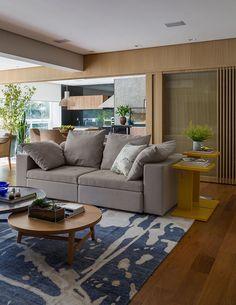 Decoração de apartamento moderno e integrado. Na sala sofá cinza, mesa lateral amarela com livros e plantas na decoração, mesa de centro de madeira e cinza, com tapete.