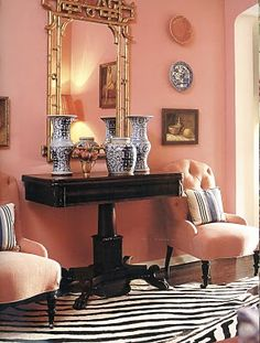 Blue and white porcelain, pink walls, tufted chairs, zebra print rug, gold framing - Mary McDonald
