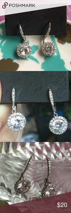 """Sterling Silver Crystal Earrings Beautiful sterling silver earrings with one large crystal surrounded by smaller crystals. Beautiful and delicate looking. Backs of earrings and hook closure are stamped with 925. No missing crystals. Hangs about 1"""" long. Jewelry Earrings"""