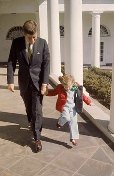 President Kennedy walking hand-in-hand with daughter Caroline on St. Patrick's Day at the White House ~ March 17th, 1961 Check out the green tie and Carolines shamrock :-) President Kennedy walking hand-in-hand with daughter Caroline on St. Patrick's Day at the White House ~ March 17th, 1961