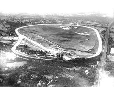 Brooklands racing circuit in Surrey. Members banking in the foreground; railway straight on right hand side and Vickers buildings on far left  by the fork into the finishing straight.