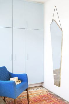 Assymetrical mirror with a golden frame designed by Design by Us.