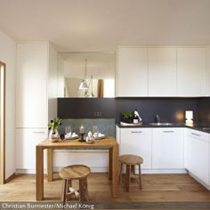 Clevere Idee: Die weisse Küche mit kontrastreichem Spritzschutz beherbergt platzsparend auch die Sitzbank inkl. Stauraum. Gesehen bei roomido.com