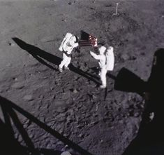 Neil Armstrong and Buzz Aldrin planting the flag of the United States on the moon.