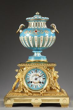 A porcelain and gilt bronze mantel clock composed of a vase with flutes patterned with polychromatic and gold coloured flowers, foliated rinceau, pearls and small enamelled flowers, on blue...