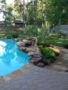 Pool Landscaping: rock waterfall in front of flowering plants